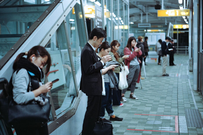 People standing on tran station with phones