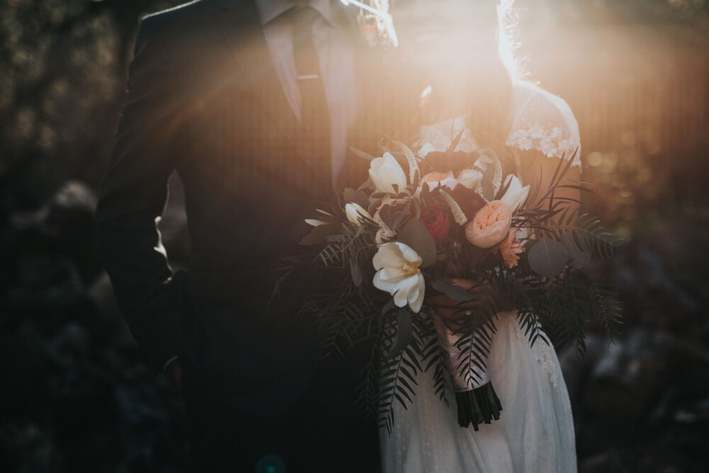 Bridal couple holding flowers in the sun