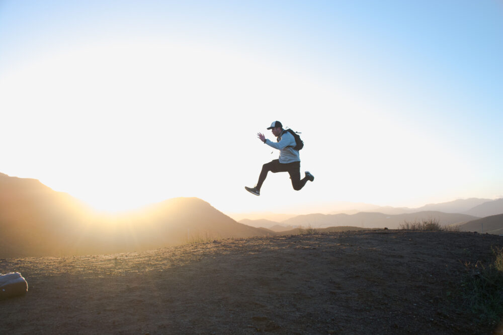 Man som hoppar på en kulle i solnedgången
