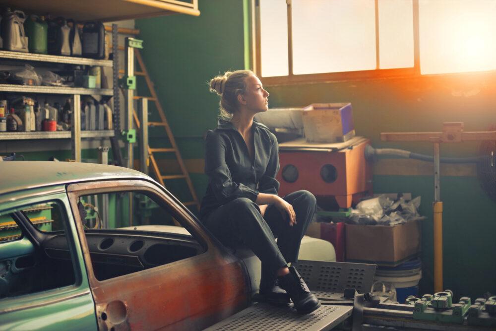 Kvinna som sitter på en bil i ett garage