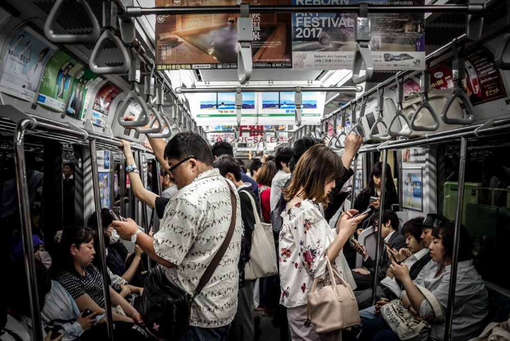 Crowded subway with people watching their phones
