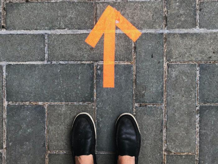 Brick street with orange arrow and feet