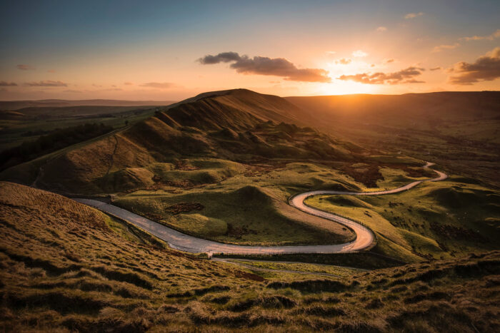 Curved road through green hills at sunset