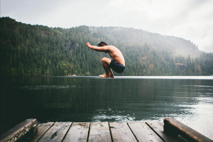 Man jumping into lake from deck